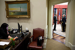 President Barack Obama talks with Gen. Martin Dempsey, Chairman of the Joint Chiefs of Staff in the Oval Office, March 11, 2015. Ferial Govashiri, Personal Aide to the President works at her desk in the Outer Oval Office. (Official White House Photo by Pete Souza)<br /> <br /> This official White House photograph is being made available only for publication by news organizations and/or for personal use printing by the subject(s) of the photograph. The photograph may not be manipulated in any way and may not be used in commercial or political materials, advertisements, emails, products, promotions that in any way suggests approval or endorsement of the President, the First Family, or the White House.
