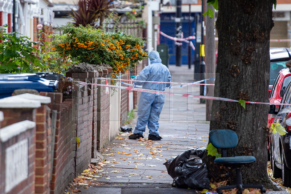 © Licensed to London News Pictures. 23/09/2019. London, UK. A forensic investigator on Abbotts Road stands next to a pool of blood on the pavement (not visible), approximately 200 meters away a man in his 20's was found injured outside a shop in The Broadway, Southall. The man was taken to hospital suffering from a stab injury; he we was pronounced dead at 05:26 BST Photo credit: Peter Manning/LNP