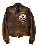 """This type A-2 flight jacket belonged to William Quinn, a bombardier attached to the 570th squadron of the 390th Bomb Group. The 570th squadron insignia patch, a joker with 4 aces behind it, is sewn to the front left of the jacket. There is a name plate above the patch which reads """"W.H. Quinn"""". On the back of the jacket the name """"Shuttle Baby"""" is painted in green and yellow above a painting of a B-17's nose turret. Below the nose turret there are 35 bombs painted in yellow, signifying Quinn's 35 successful missions.  Also notice the Russian Red Star symbol, denoting a """"shuttle run"""" to Russian controlled territory, and a windmill and white food bag, denoting participation in Operation Chowhound, the late-war effort to drop food to the starving Dutch people."""