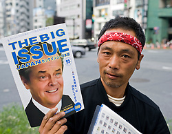 Japanese homeless man selling The Big Issue magazine on the street in Tokyo Japan