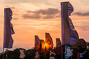 Sunset, as flags fly in the main arena.WOMAD 2014, festival of world music and dance, Charlton Park, Wiltshire. UK.