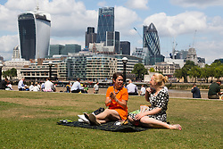 © Licensed to London News Pictures. 15/07/2014. London, UK. Two women enjoy a picnic in the sunshine near Tower Bridge in central London this lunchtime. Photo credit : Vickie Flores/LNP