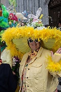 New York, NY, USA-27 March 2016. A woman wears a very large brimmed hat, bordered by yellow feathers, and topped with an Easter Bunny, on the steps of St. Patrick's Cathedral at the annual Easter Bonnet Parade and Festival.