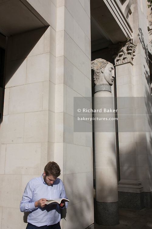 Educated man reading book with City of London sculpture.