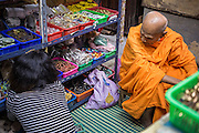 05 OCTOBER 2012 - BANGKOK, THAILAND:  A Buddhist monk shops for amulets in Bangkok. Hundreds of vendors sell amulet and Buddhist religious paraphernalia to people in the area north of the Grand Palace near Wat Maharat in Bangkok.        PHOTO BY JACK KURTZ