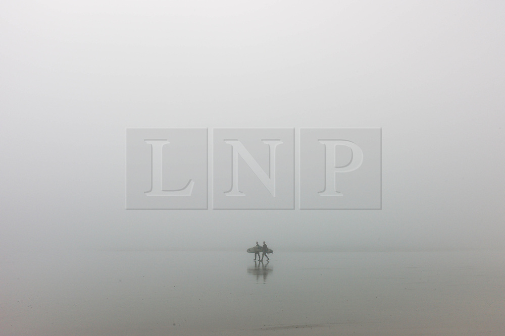 © Licensed to London News Pictures. <br /> 08/05/2016. <br /> Saltburn by the Sea, UK.  <br /> <br /> Two surfers walk towards the water as they head for a surf as heavy fog shrouds the coastline at Saltburn by the Sea in North Yorkshire as much of the country enjoys the hottest temperatures of the year so far.<br /> <br /> Photo credit: Ian Forsyth/LNP