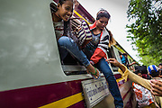 16 JUNE 2014 - ARANYAPRATHET, THAILAND: Cambodian women jump out the window of the train at the train station in Aranyaprathet, Thailand. More than 150,000 Cambodian migrant workers and their families have left Thailand since June 12. The exodus started when rumors circulated in the Cambodian migrant community that the Thai junta was going to crack down on undocumented workers. About 40,000 Cambodians were expected to return to Cambodia today. The mass exodus has stressed resources on both sides of the Thai/Cambodian border. The Cambodian town of Poipet has been over run with returning migrants. On the Thai side, in Aranyaprathet, the bus and train station has been flooded with Cambodians taking all of their possessions back to Cambodia. PHOTO BY JACK KURTZ