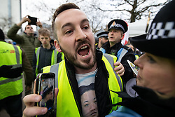 "© Licensed to London News Pictures . 09/02/2019. Manchester , UK . JAMES GODDARD (wearing a Kim Jong Un shirt) live streams video using his mobile phone as he leads a "" Yellow Vest "" protest in Manchester City Centre . The yellow vest concept has been adopted from French demonstrators by some British groups in support of Brexit , Donald Trump and former EDL leader Stephen Yaxley-Lennon - aka Tommy Robinson . A similar demonstration in the city in January was ridiculed after protesters were kettled by police in front of a branch of Greggs the Baker . Photo credit : Joel Goodman/LNP"