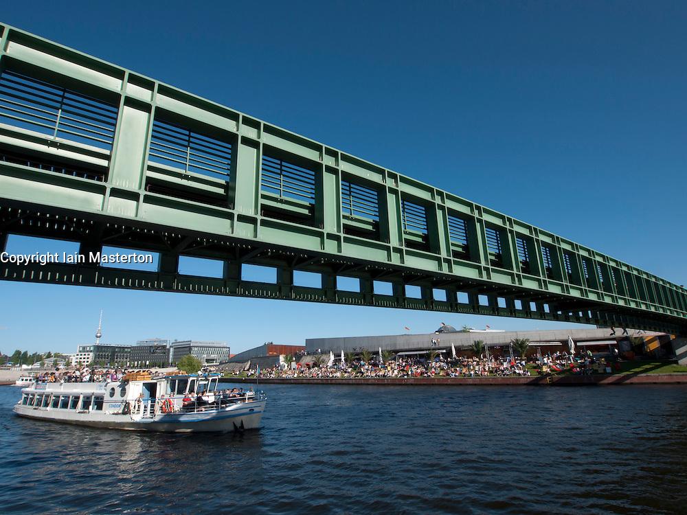 modern footbridge across Spree River with busy riverside bar to rear in Berlin Germany