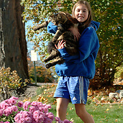 Isabelle, 9, holds her grandmother's cat as their little furry friwnd got loose from the housewhile they were cleaning up the yard