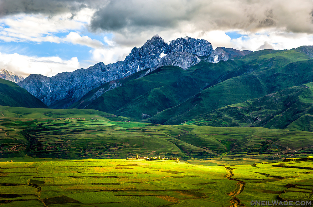 A Tibetan Village sits peacefully in green barely fields below a formidable mountain near Ganzi, Tibet.