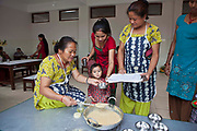A female Nepalese woman serves nutritious food in a small metal bowl to a young child in the dining room at the Friends of Needy Children Nutritional Rehabilitation Centre, Kathmandu, Nepal.  The child is being helped by their mother and the food portion is recorded by a woman with a clipboard and paper.  The child is an inpatient at the centre and receiving intensive treatment for malnutrition. The centre has recently been built to provide healthcare to malnourished children and education to mothers about nutrition and childcare.