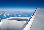 Airplane wing with blue sky and clouds somewhere over an ocean