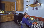 Amish young adult woman works at table in Amish home kitchen, Lancaster Co, PA