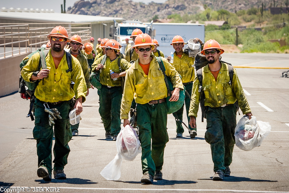 26 JUNE 2005 - CAVE CREEK, AZ: Members of the Horseshoe Meadow Hotshots, from the Sequoia National Forest in California, walk back to their vehicles after getting off a Bell Super 205 helicopter at the Skyranch at Carefree, a private airport in Carefree, after returning from the Cave Creek Complex fire line Sunday afternoon. The airport has been allowing the team fighting the Cave Creek Complex fires to use their facilities as the helibase for the fire. The Cave Creek Complex fire was the third largest wildfire in the state of Arizona to date, after the Rodeo-Chediski fire and Wallow Fire. The fire started on June 21, 2005 by a lightning strike during a monsoon storm and burned 243,950 acres (987.2 km2).   PHOTO BY JACK KURTZ