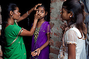 Sangita, 40, (left) is applying some make-up to the eye of her daughter Jyoti, 12, (centre) while Poonam, 11, (right) is looking at them while standing in the front yard of the family's newly built home in Oriya Basti, one of the water-contaminated colonies in Bhopal, central India, near the abandoned Union Carbide (now DOW Chemical) industrial complex, site of the infamous '1984 Gas Disaster'.