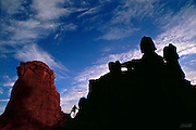 A lone hiker watches the first touch of sunrise wash a desert sanstone butte near Goblin Valley, Utah.