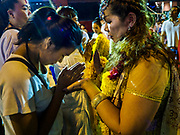 30 SEPTEMBER 2017 - BANGKOK, THAILAND: Women finish praying together during the Navratri parade in Bangkok. Navratri is a nine night (10 day) long Hindu celebration that marks the end of the monsoon and honors of the divine feminine Devi (Durga). The festival is celebrated differently in different parts of India, but the common theme is the battle and victory of Good over Evil based on a regionally famous epic or legend such as the Ramayana or the Devi Mahatmya. Navratri is celebrated throughout Southeast Asia in communities that have large Hindu population. Bangkok's celebration of Navratri was subdued this year because Thais are still mourning the death of Bhumibol Adulyadej, the Late King of Thailand, who died on October 13, 2016.      PHOTO BY JACK KURTZ