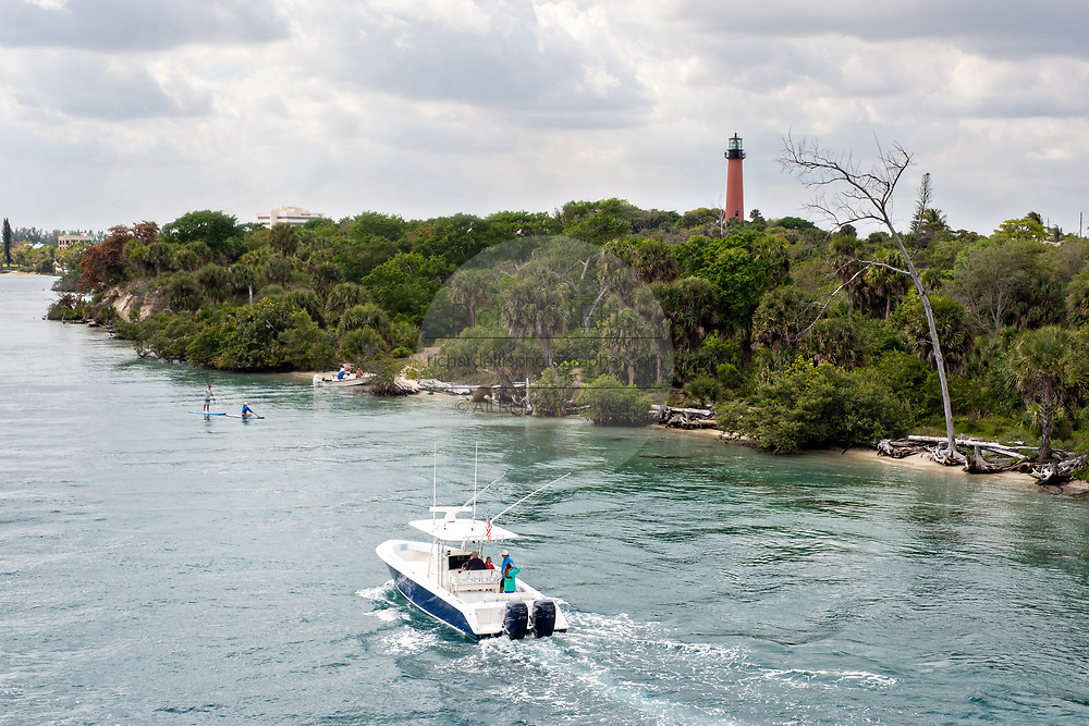 Boats travel along the Indian River past the Jupiter Inlet Lighthouse at the South Beach Bridge in Jupiter, Florida.