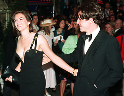 """Actor Hugh Grant arrives with actress girlfriend Elizabeth Hurley for the chaity premiere of """"Four Weddings and a Funeral"""" in which he stars."""