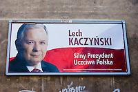 "bill board poster for lech kaczynski showing his face and red and white background in krakow poland. the writing reads ""lech kaczynski - silny prezydent uczciwa polska"""