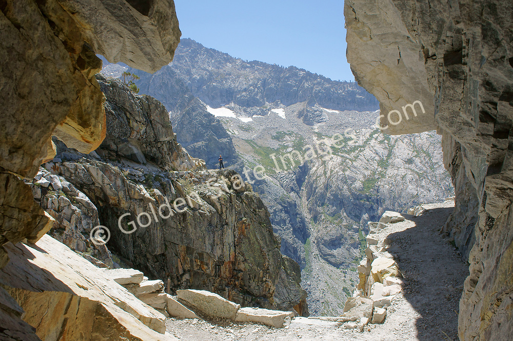 The hiker in the background nearly disappears under the sheer scale of the mountains.<br /> <br /> The only trail tunnel in the High Sierra.