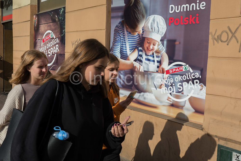 Young modern Polish women walk past a poster outside a Spar supermarket showing the stereotyping of gender: a mother and her daughter enjoying baking in the kitchen together, on 23rd September 2019, in Krakow, Malopolska, Poland. The poster translates as: My neighborhood ,my spar.