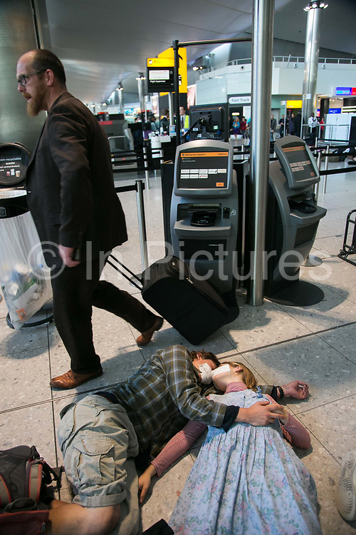 Protesters against a possible third runway at Heathrow and aviation in general for contributing to climate change stage a flash mob die-in and  theatrical 'Frequent-fliers-high-polluters club theater at terminal 2 at Heathrow, London, Oct 1st 2016.
