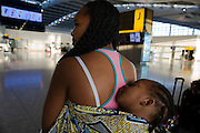 A young African mother allows her sleeping baby some well-earned rest on her back at Heathrow Airport's Terminal 5.