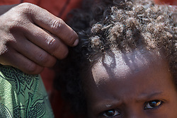 27 January 2019, Burka Dare IDP site, near Micha, Seweyna woreda, Bale Zone, Oromia, Ethiopia: Oromo woman Halima Ismael caresses her child outside their home in the Burka Dare IDP site. The Lutheran World Federation supports internally displaced people in several regions of Ethiopia, through emergency response on water, sanitation and hygiene (WASH) as well as long-term development and empowerment projects, to help build resilience and adapt communities' lifestyles to a changing climate.