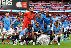 Manchester City's players pose with the Community Shield trophy after the Community Shield match at Wembley Stadium, London.