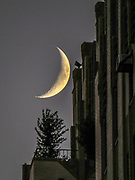 The moon crescent shines over the building.