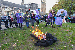 © Licensed to London News Pictures. 05/11/2019. London, UK. Women's Pension reformers demonstrate outside Parliament by burning an effigy of Pension's Minister Guy Opperman on Parliament Square. The Pensions act increases the female state pension age from 60-65. Photo credit: Alex Lentati/LNP