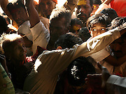 """A young girl's frightened eyes are visible amidst the crush of worshippers as her father tries to carry her into the Yellamma Temple in Saundatti, India, on the first day of the Yellamma Jatre (festival).  The Yellamma Jatre is an annual gathering of half a million Yellamma pilgrims who converge on the temple to worship the deity.  Amongst the rituals performed to appease Yellamma, young girls are dedicated as Devadasi or """"temple servants"""".  These young girls are married to the deity and must spend their lives serving the deity which includes catering to the sexual needs of men in the community.  They may not marry a mortal and often end up working in brothels in India's urban centers. While the dedication ceremonies used to be performed in public at the Jatre and included parading the young girls naked through the crowds or covered in """"neem"""" leaves, due to the Devadasi Prohibition Act, they are now performed in secret."""