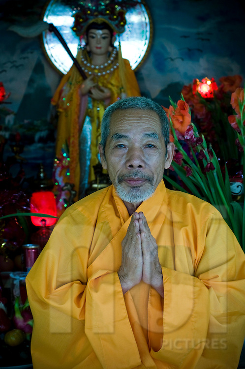 Portraiture of a buddhist monk in a pagoda of Khanh Hoa province, Vietnam, Asia.  He's folding his hands in an attitude of prayer.He wears an orange robe