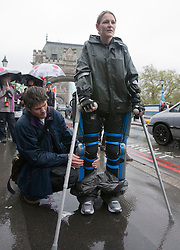 © licensed to London News Pictures. London, UK 29/04/2012. Claire Lomas, who was paralysed from the chest down after an accident, having her robotic suit checked while she walks the London Marathon to raise money for Spinal Research. On her 8th day of Marathon walk, she passes Tower Bridge under heavy rain (29/04/12). Photo credit: Tolga Akmen/LNP