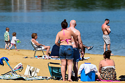 © Licensed to London News Pictures. 20/05/2020. LONDON, UK.  A woman applies sunscreen as members of the public take advantage of the easing of certain coronavirus pandemic lockdown restrictions to enjoy the sunshine and warm weather at the beach at Ruislip Lido in north west London.   The forecast is for temperatures to rise to 29C, the hottest day of the year so far.  Photo credit: Stephen Chung/LNP