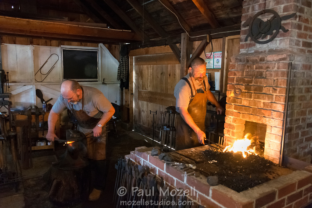 Two blacksmiths work in iron and steel to fashion hand tools at the Freyburg Fair in Maine.
