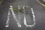The word NO fading on a south London housing estate road surface. We see a detail of the ground, where the stencil has been painted a while ago, now fading after years of weathering as well as weeds now growing from old tarmac. The estate is in the London borough of Southwark, a mile or so south of the river.
