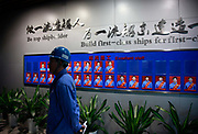 A man stands near a wall adorned with photographs of model workers at the China State Shipbuilding Corp.'s (CSSC) Longxue Shipyard in Guangzhou, Guangdong Province, China, on Sunday, Nov. 13, 2011. China is the world's biggest shipbuilder, however recent economic downturns have caused a glut in supplies.