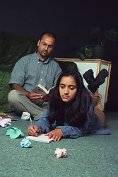 Teenage girl lying on floor writing letter; with father reading book behind her,