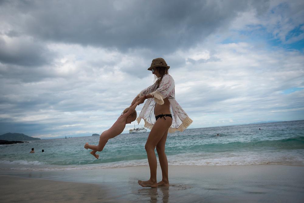 Bali, Indonesia - February 17, 2017: Natali and her son Kiricou at White Sand Beach in Padangbai, Bali.