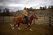 """Regis Hogan, 30, attempts to break a wild horse on his land near Lodge Grass, MT along the Crow Indian Reservation. """"It takes awhile to break them,"""" said Hogan as he circled around on the skiddish horse. """"With some love and persistences the wild ones end up being the best you could have."""""""