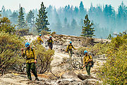 U.S. Forest Service wildland firefighters head back down to Wawona Road near Tunnel View after cutting off the Ferguson Fire's fuel at Yosemite National Park on Wednesday, Aug. 8, 2018, in Mariposa County, Calif.