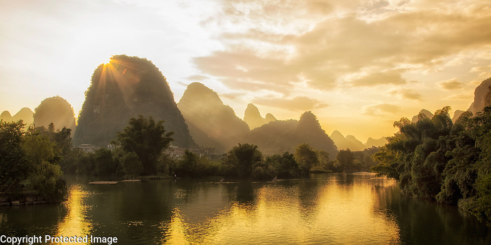 This photo was taken in 2015 when my wife and I were on a bicycle trip through China.  At the end of the day as we rode into the city of Yangshuo I could tell the evening was going to treat us to a great sunset.  During the afternoon we had ridden about 30 miles in the hot, humid weather.  Everyone was tired and the entire riding crew was ready to get to their hotel rooms.  However I remembered a bridge we had ridden over earlier in the day about 5 miles away from the hotel that had a great view of the Karst Mountains.  I went to the room and grabbed my backpack with all my camera gear and headed out.  I knew I didn't have much time to spare so I rode as quickly as I could.  I arrived at the river drenched in sweat but with the sun still hanging low in the sky.  I quickly assembled my tripod and camera and captured this image.  Though the ride back to the hotel was more than a bit tense.  Evening had set in and I was all by myself.  I don't speak the language and I don't know how to read Chinese symbols.  In the dark I strained to remember the route back to the hotel but after a few anxious moments and five miles of uncertainty I made it back safely.