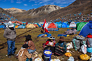 Women clean potatoes to prepare food for a group of pilgrims, in the backgroud, hundreds of tents that pilgrims place to stay for 3 or 4 days in the valley of the sanctuary of the Lord of Qoyllur Rit'i , a festival that takes place every year in Cusco, Peru.