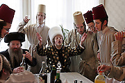 During the Jewish festival of Purim A group of Orthodox Jewish boys from the Viznitz Yeshiva (school) in fancy dress visit local businessmen to collect money for their school. The Purim Rabbi (centre) leads the group with a song, they drink alcohol at every house they visit during the day.