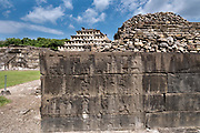 Carved relief panels on the walls of the South Ballcourt with the Pyramid of the Niches behind at the pre-Columbian archeological complex of El Tajin in Tajin, Veracruz, Mexico. El Tajín flourished from 600 to 1200 CE and during this time numerous temples, palaces, ballcourts, and pyramids were built by the Totonac people and is one of the largest and most important cities of the Classic era of Mesoamerica.