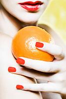 beautiful caucasian woman portrait holding a mandarin  orange tangerine fruit sutdio on yellow background