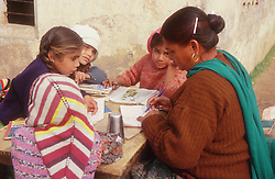 Teacher with pupils working at table outdoors in primary school in Patiala; Punjab; India,